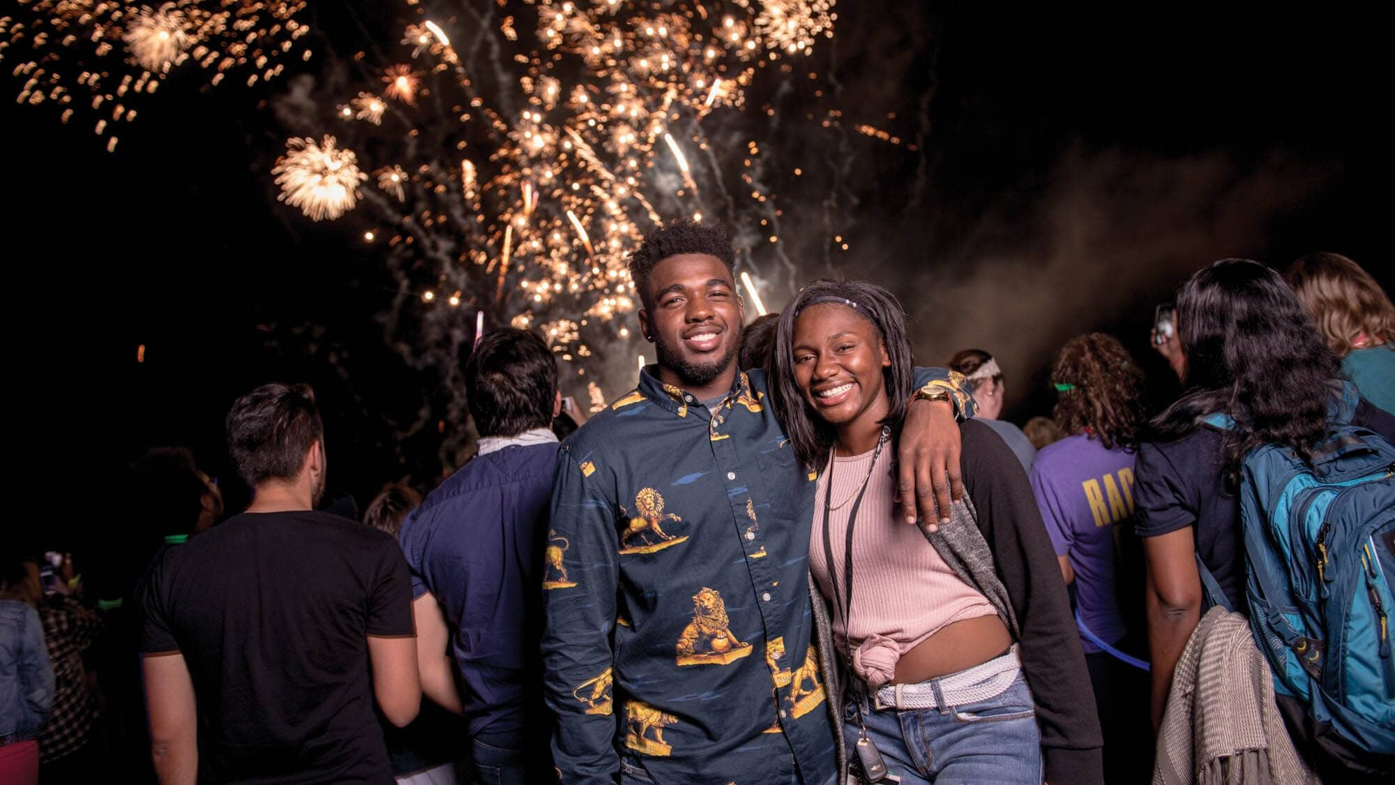 Two students smiling to the camera with fireworks in the background.