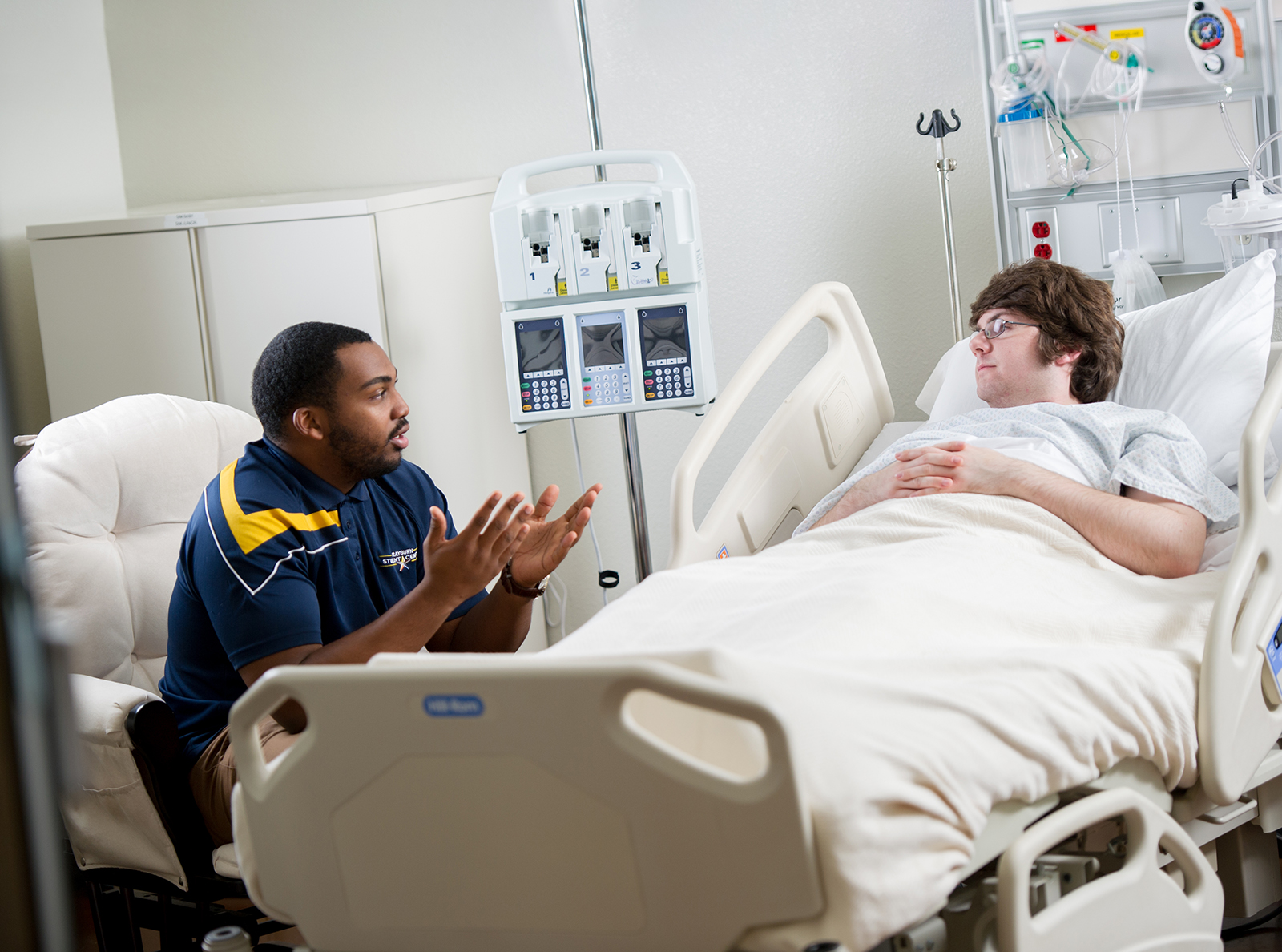 A student laydown in a hospital bed listening to a counselor.