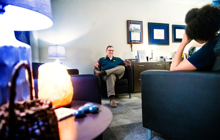A counselor talking to a student sitting down on separate couches.