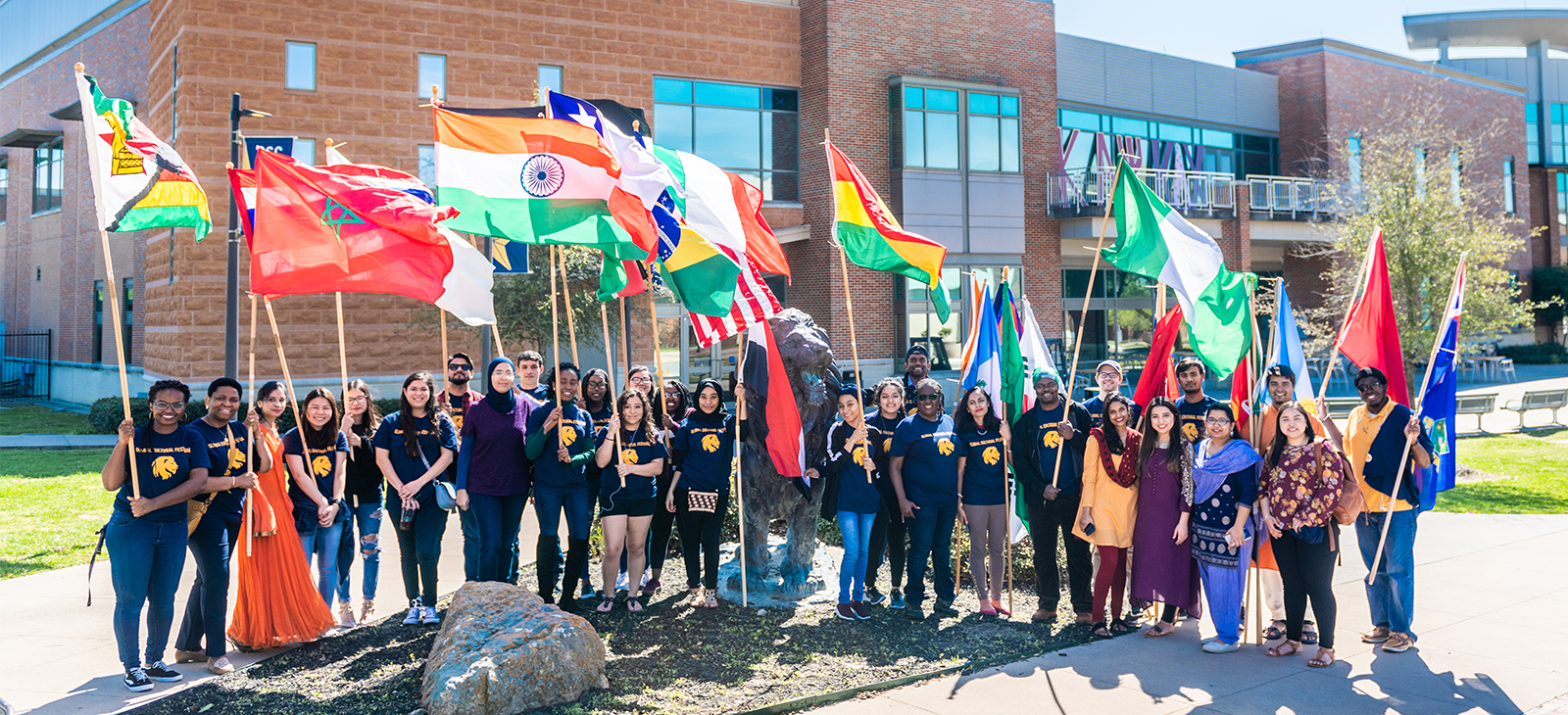 Student smiling holding flags from different countries.