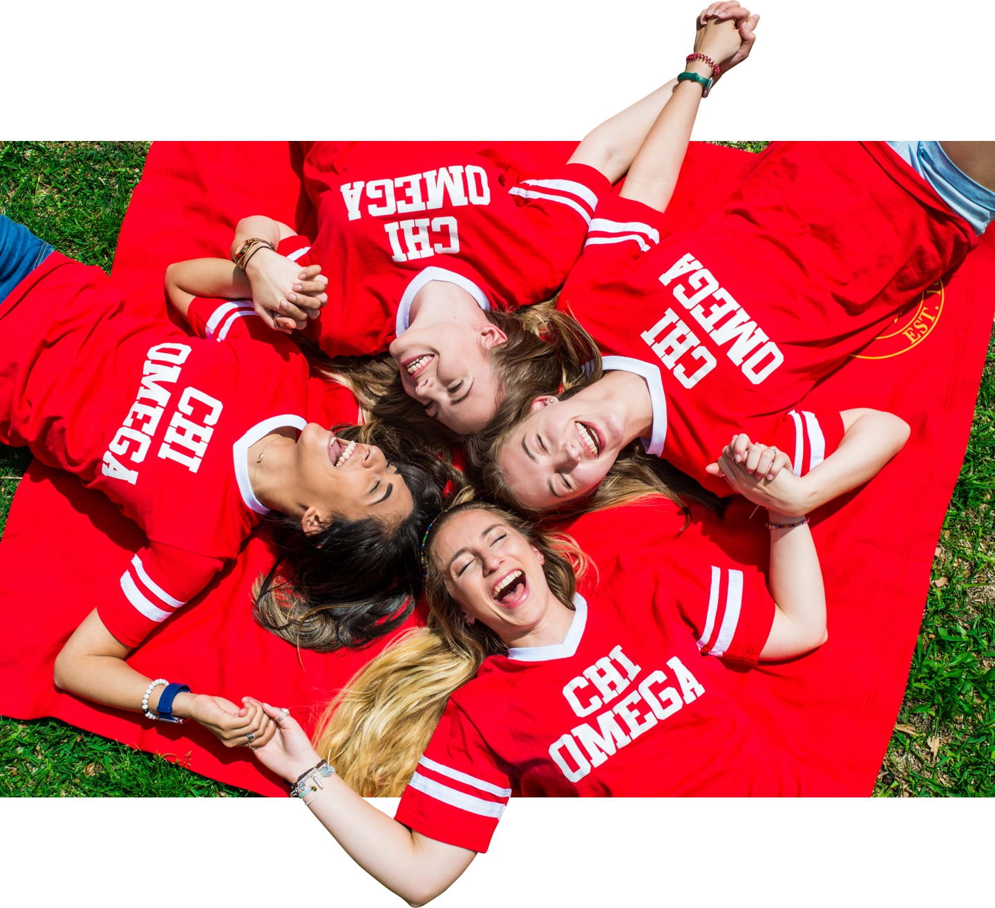 Four Chi Omega sorority students laying on the grass holding hands.