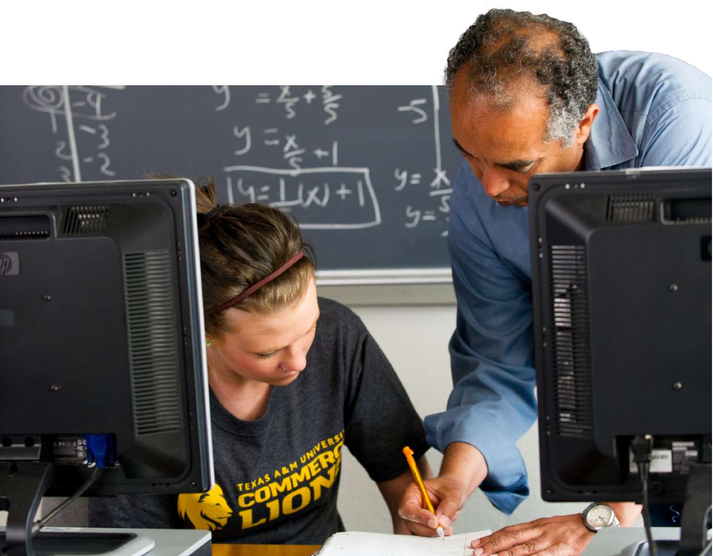 A math professor explaining to a student in the computer lab.