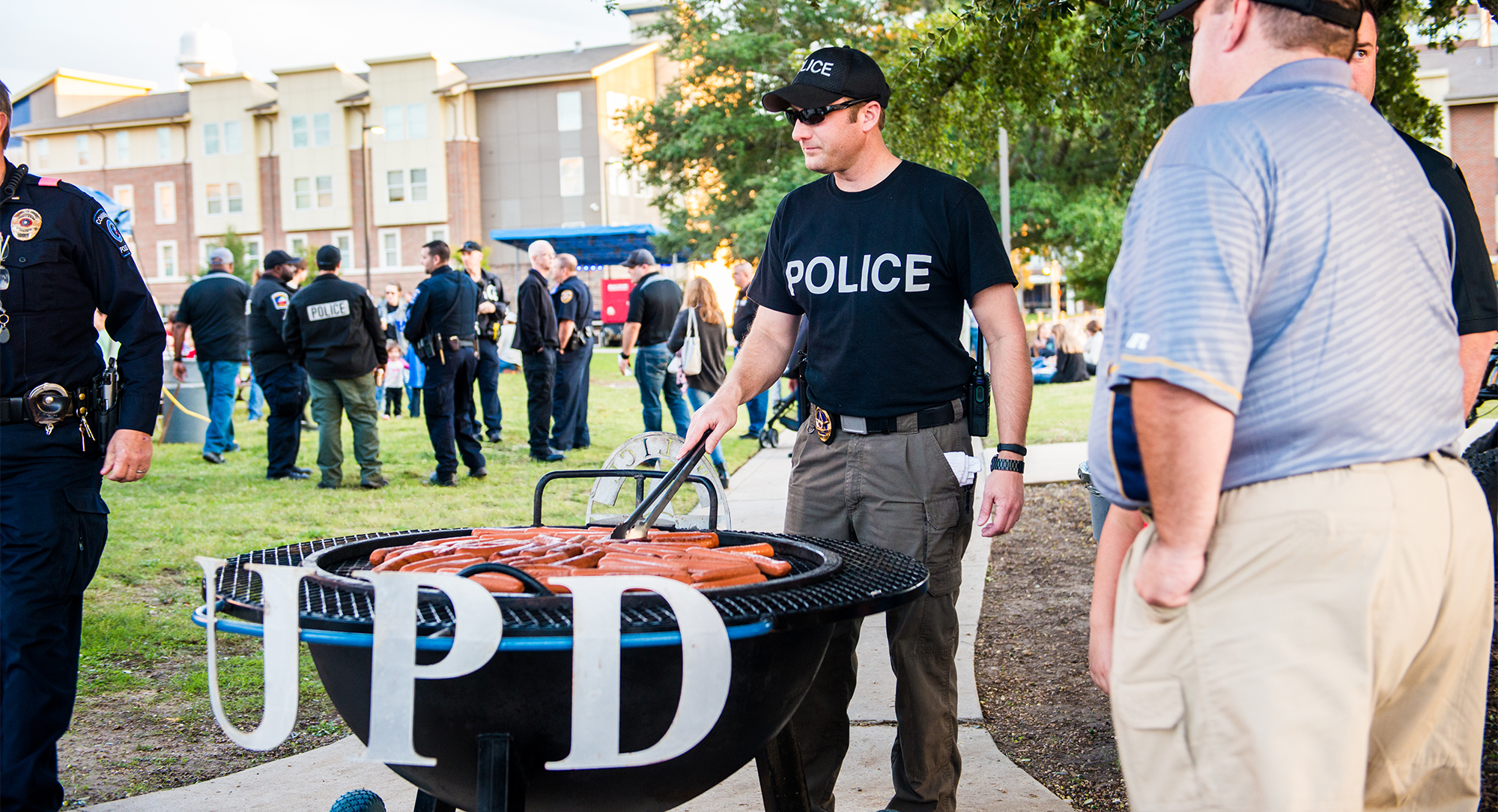 Police officer grilling hot dogs at a community engagement event.