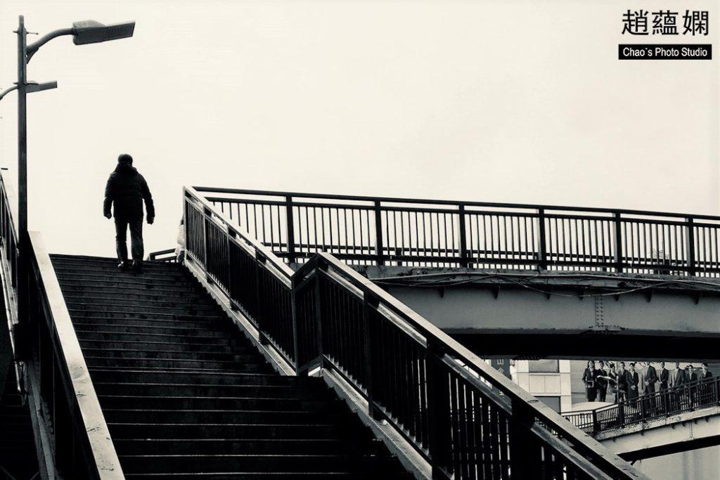 一人走在天橋上,姿勢有孤寂感。