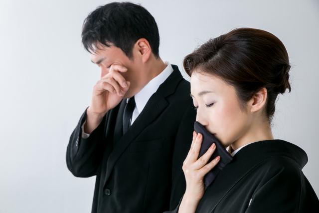 葬儀で泣く男女