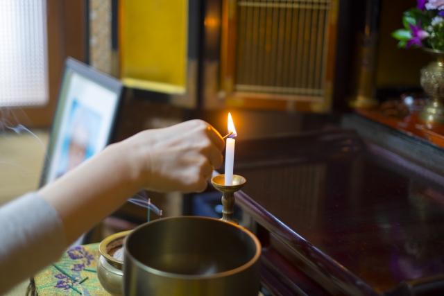 仏壇のロウソクに火をともす手