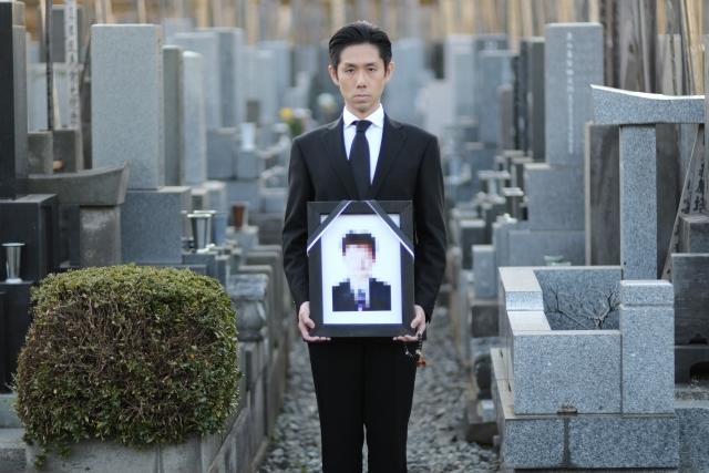 遺影を持つ喪服男性
