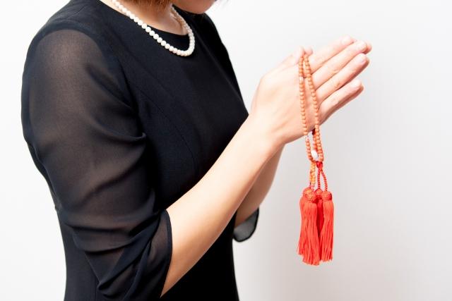 数珠を持つ喪服姿の女性