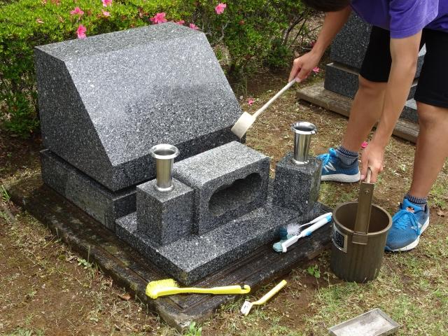 お墓掃除を行う男性