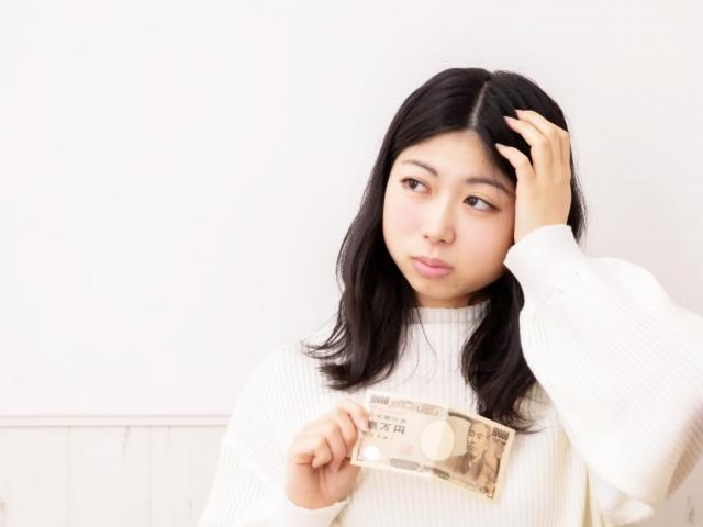 お金をもって考える女性