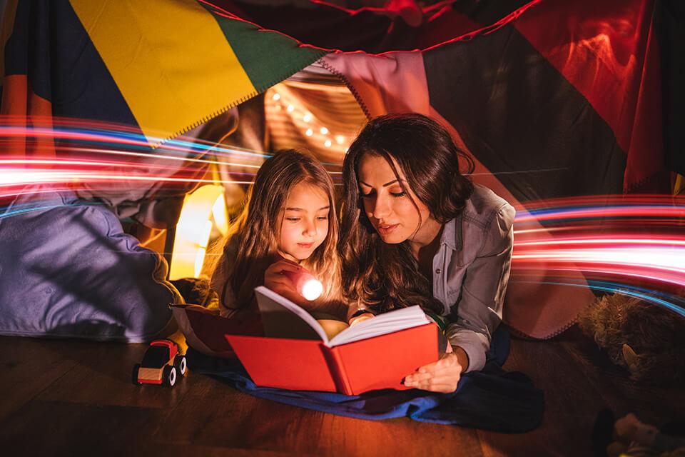 Mujer joven con niña viendo un libro con una linterna