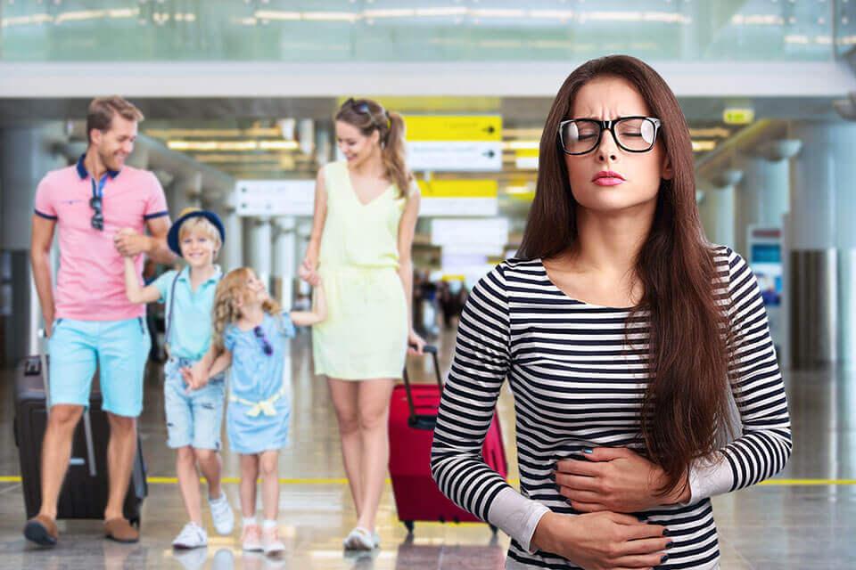 Mujer se lleva las manos al estomago con expresión de dolor en su rostro, personas detrás de ella pasean felices
