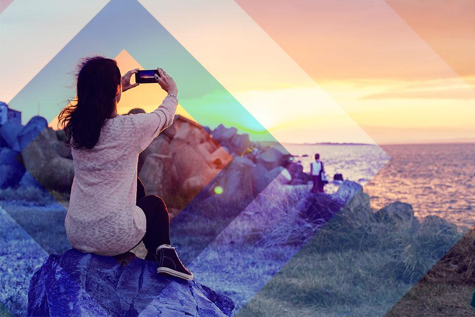 Mujer tomando foto con su celular al atardecer