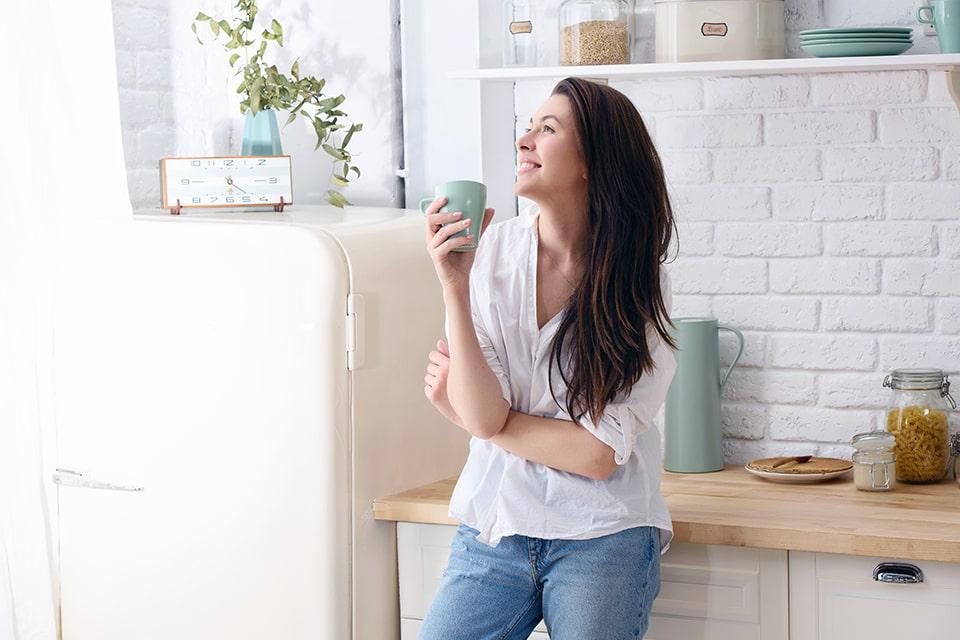 Mujer tomando café en la cocina