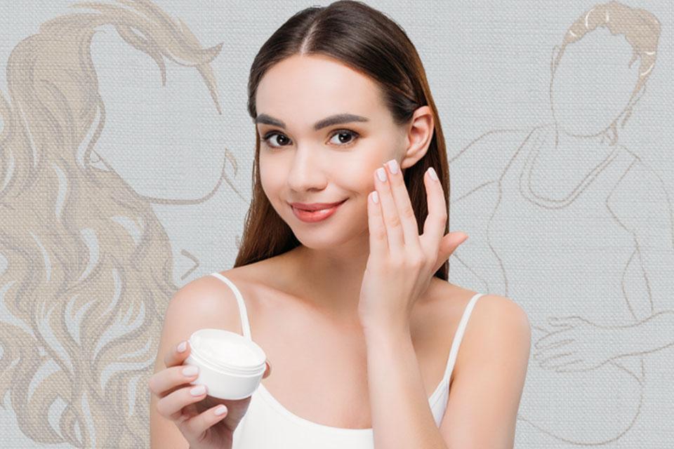 Mujer joven aplicandose crema en el rostro