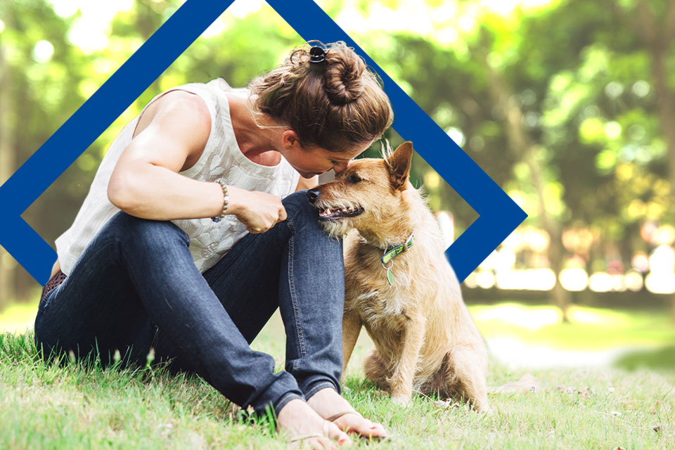 Mujer y su perro disfrutando de un día en el parque