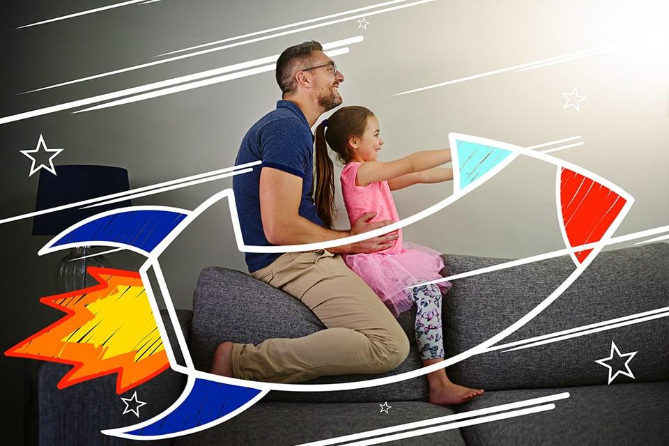 Padre jugando con su hija en un cohete imaginario