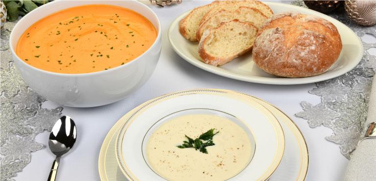 Mesa con tazón de crema de tomate rostizado, plato con crema irlandesa tradicional y pan rústico