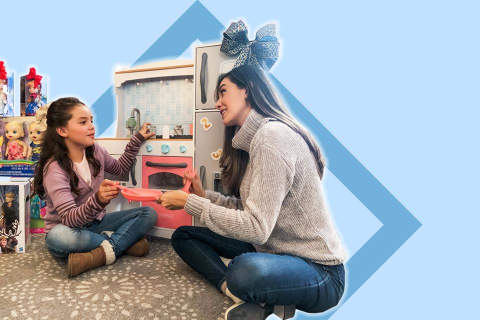 Mujer y niña jugando con regalos navideños