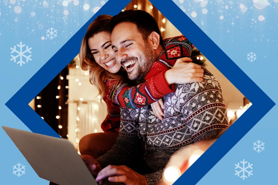 Primer plano con motivos navideños de una pareja viendo la pantalla de una laptop