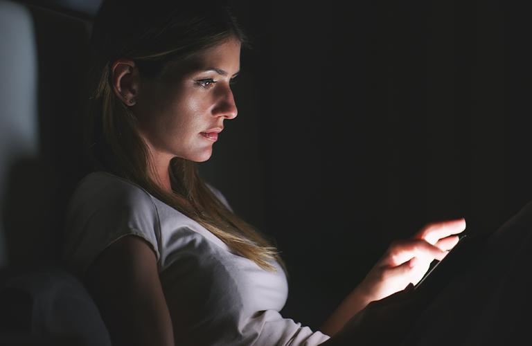 Mujer usando tablet en la noche