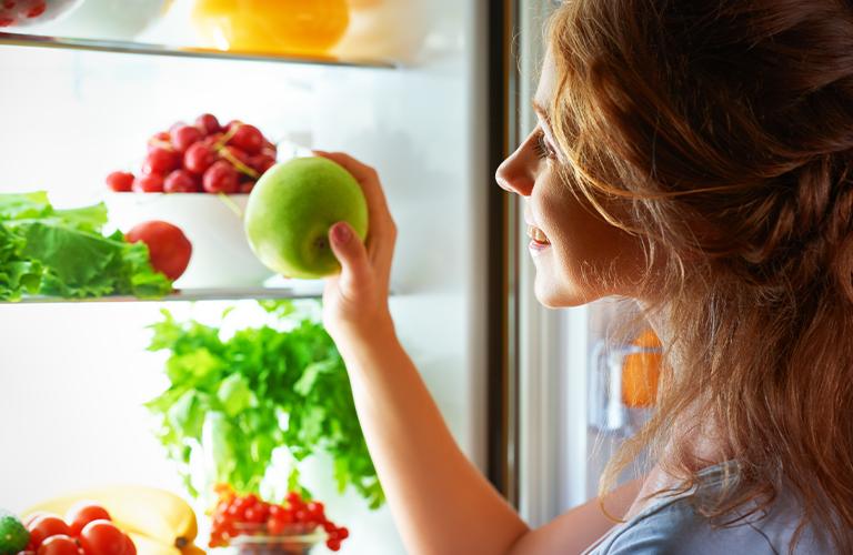 Mujer sacando una manzana del refrigerador