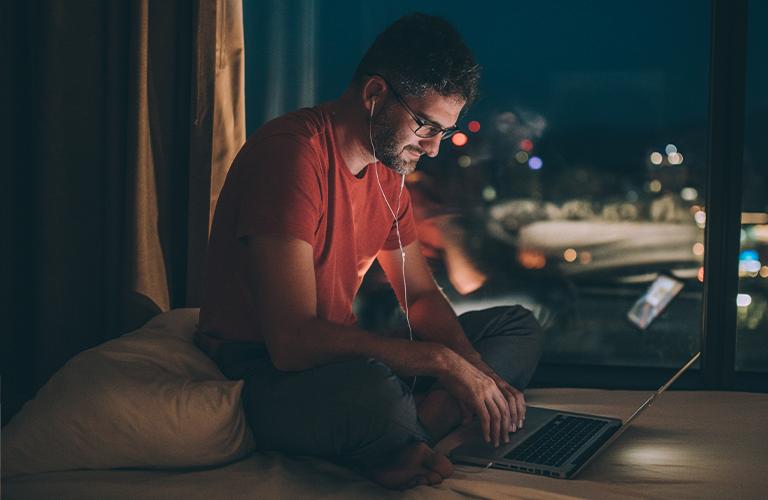 Hombre trabajando con su laptop en la cama de noche