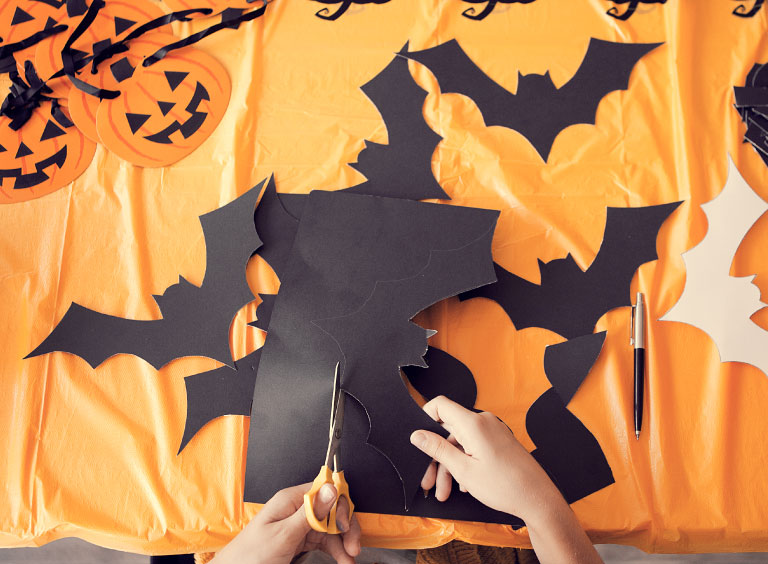 Niño recortando murciélagos de papel