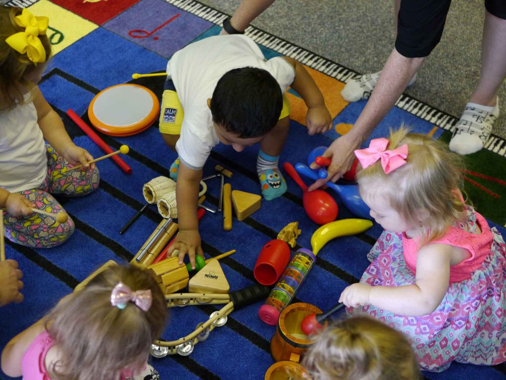 Toddlers playing with instruments in music class, listening to one of the 10 Free Songs in our download