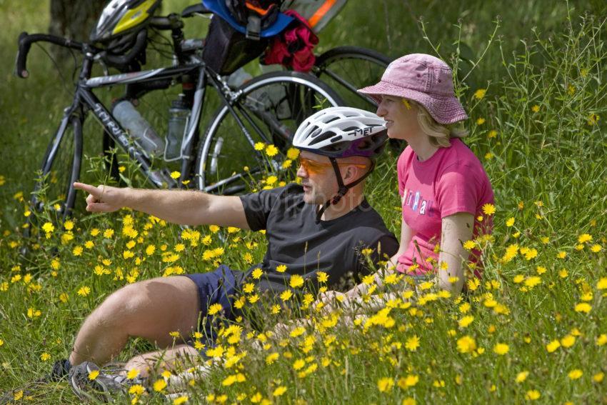 Cyclist Take A Break Amongst The Buttercups In Argyll