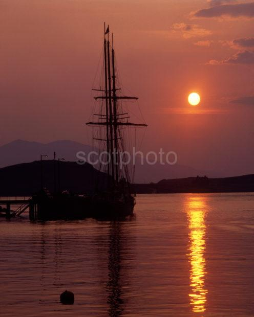 Sunset Over Tall Ship In Oban Bay With The Hills Of Mull