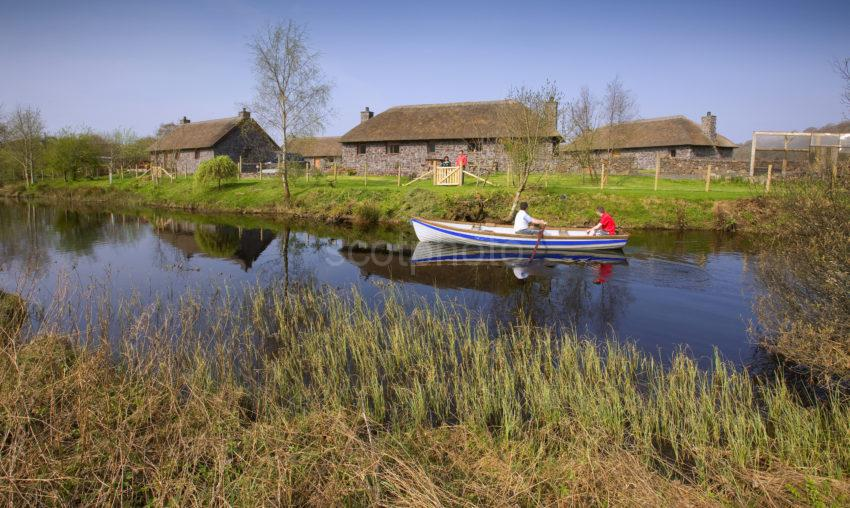 I5D1222 Clan Cottages With Passing Rowing Boat