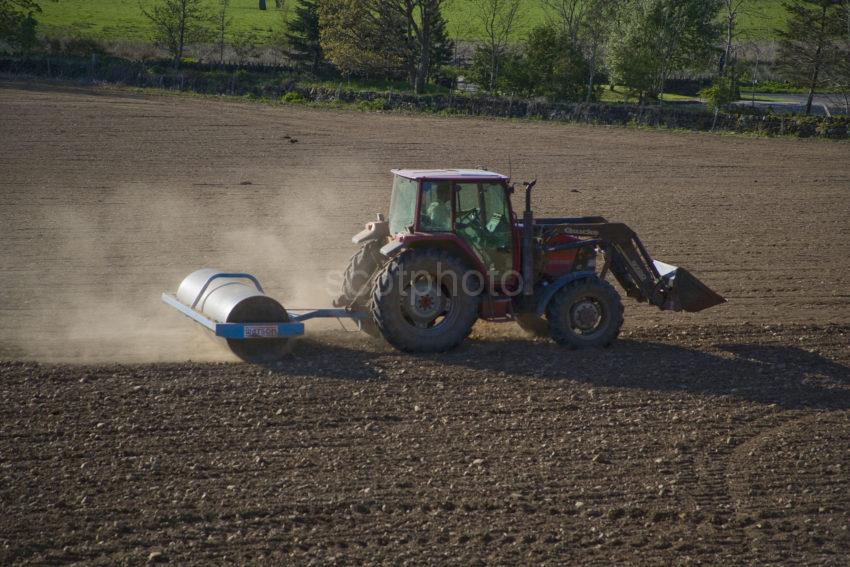 WY3Q4877 Farmer In Tractor Prepares A Field For Planting In Argyll