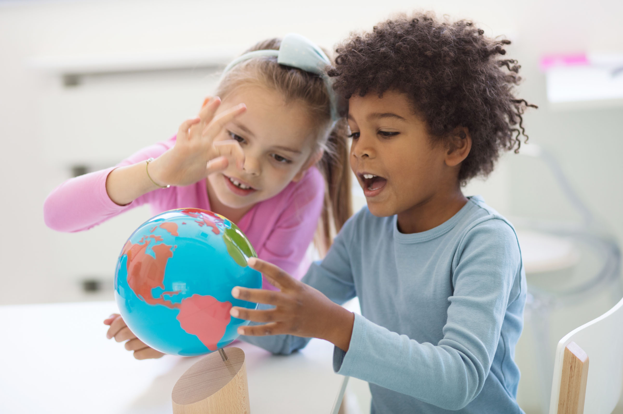 Preschool Pals looking at a globe