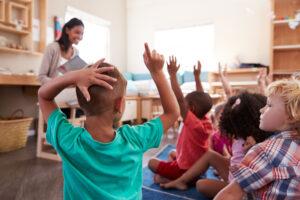 Preschool Pals children raising hands