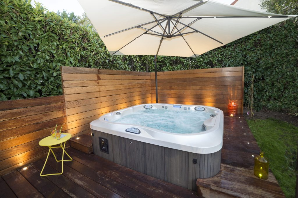 Jacuzzi hot tub in a backyard patio with chairs and umbrella