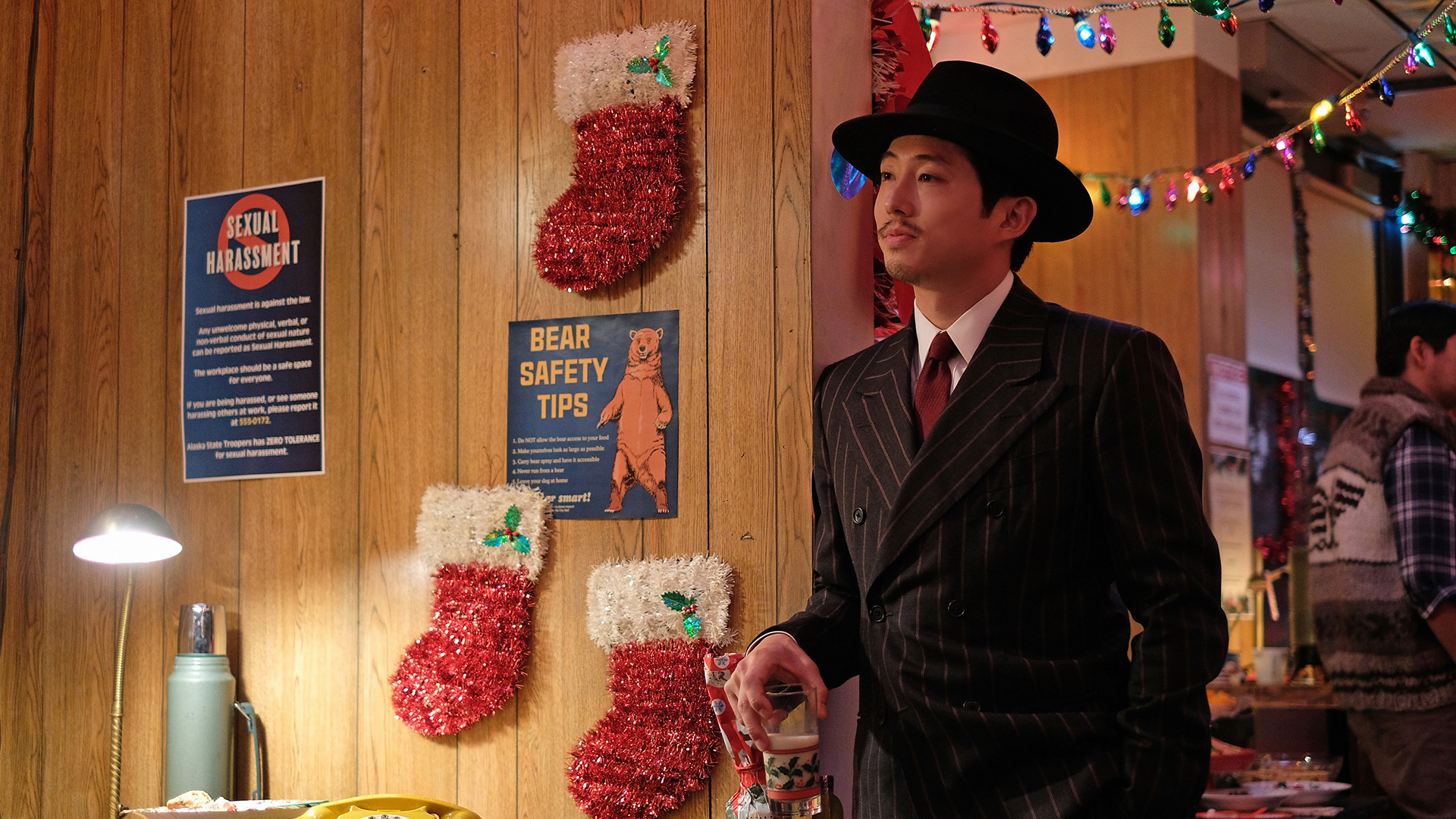 "Steven Yeun stands at the edge of a Christmas party in the episode ""A. Traveler"" in the rebooted Twilight Zone series."