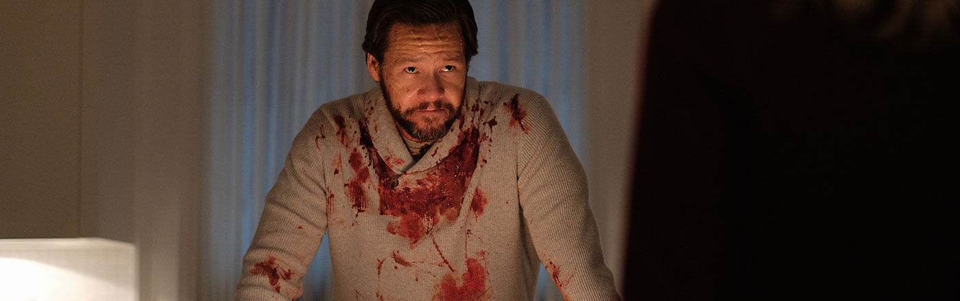 "Ike Barinholtz stands behind a table, with blood on his sweater in the episode ""Not All Men"" in the rebooted Twilight Zone series."
