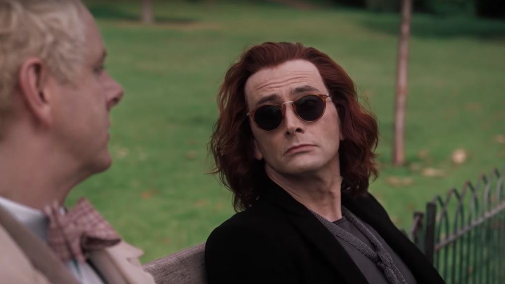 Anthony Crowley sits on a bench in a park with Aziraphale.