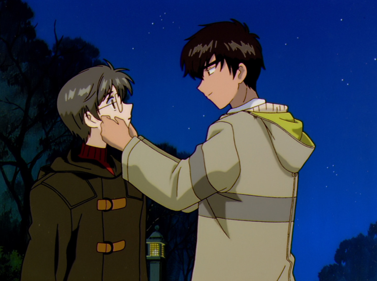 Touya and Yukito are standing outside at night. Touya is pinching Yukito's cheeks affectionately.