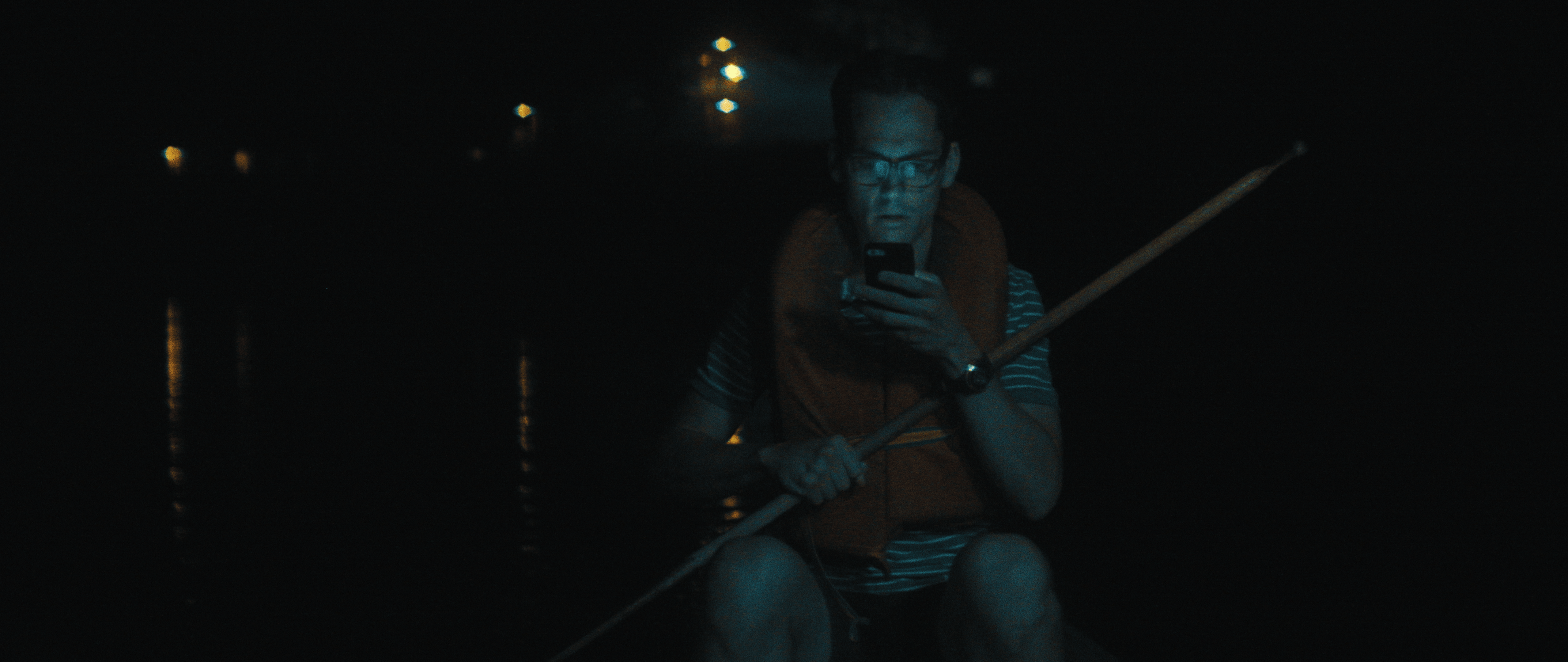 Camp Wedding film still where a man is on a lake staring at his phone.