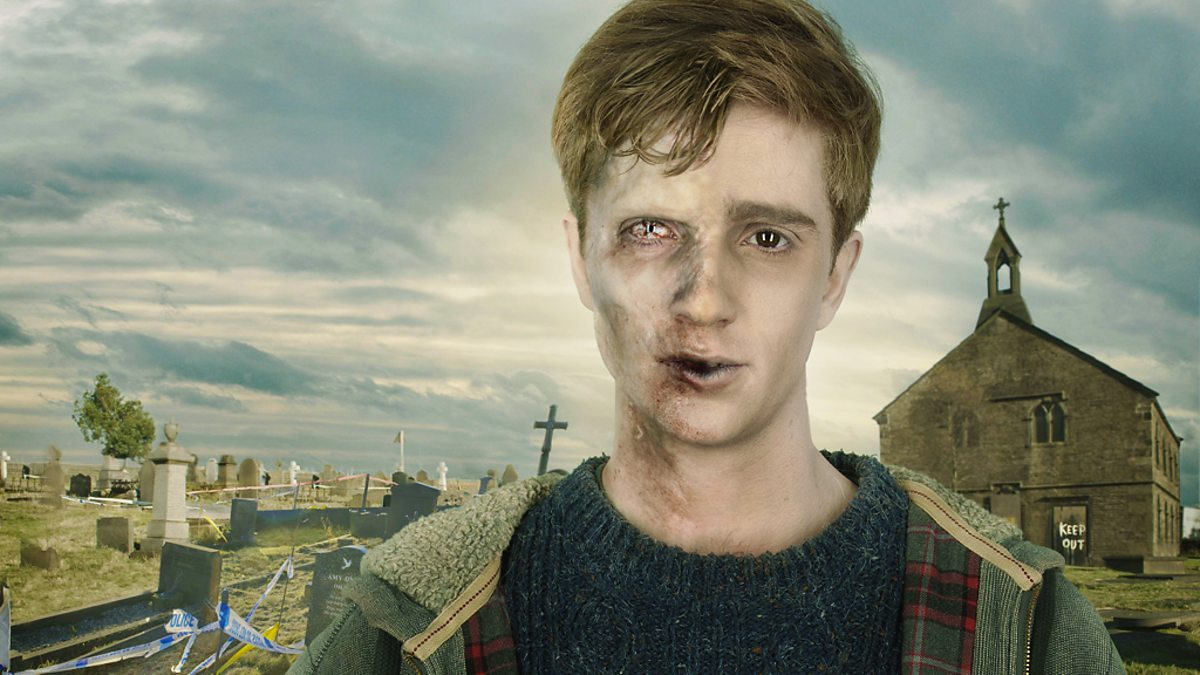 In the Flesh Season 1 cover of Kieren standing in front of a church cemetery. His face is half human, half zombie.