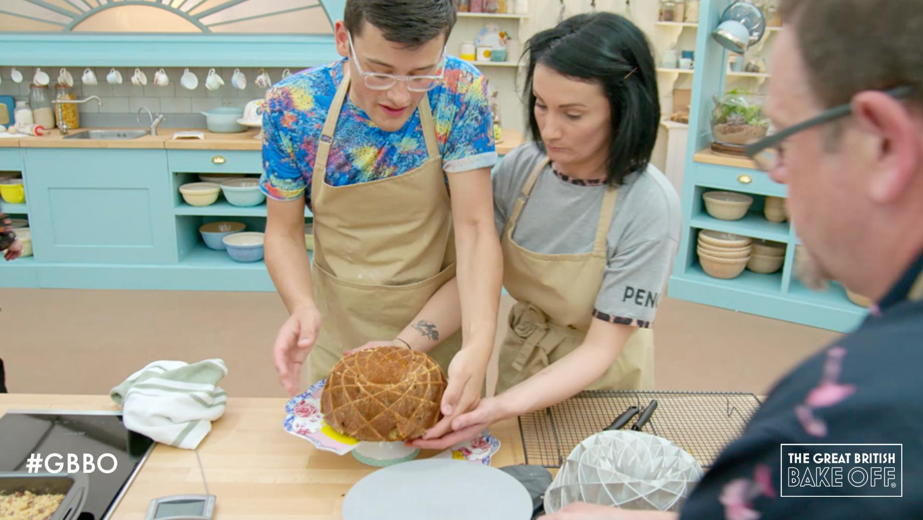A contestant on the Great British Baking show helps another whose cake is about to fall off of a plate.