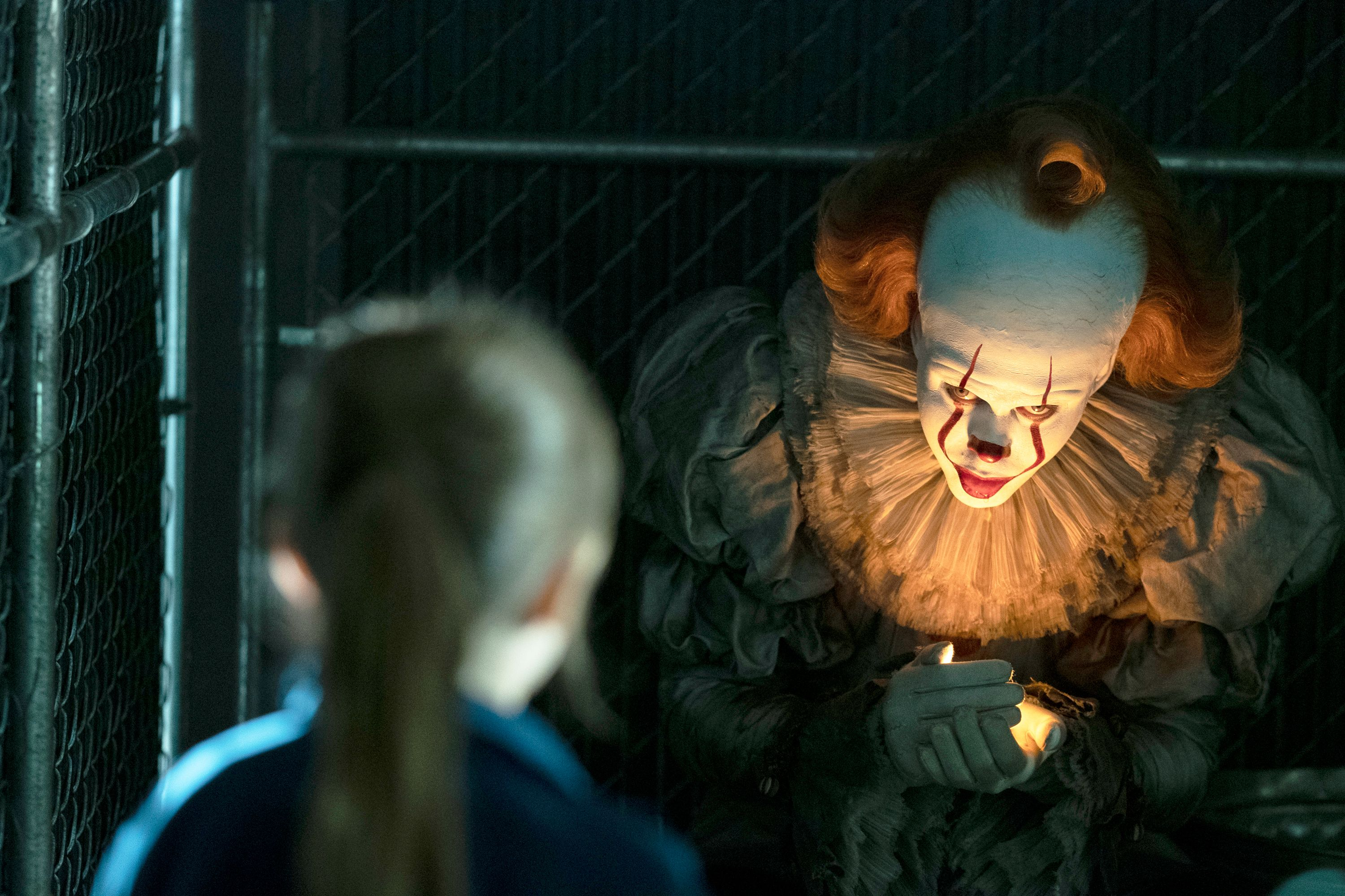 Pennywise holding a firefly in his hand trying to lure in a little girl.