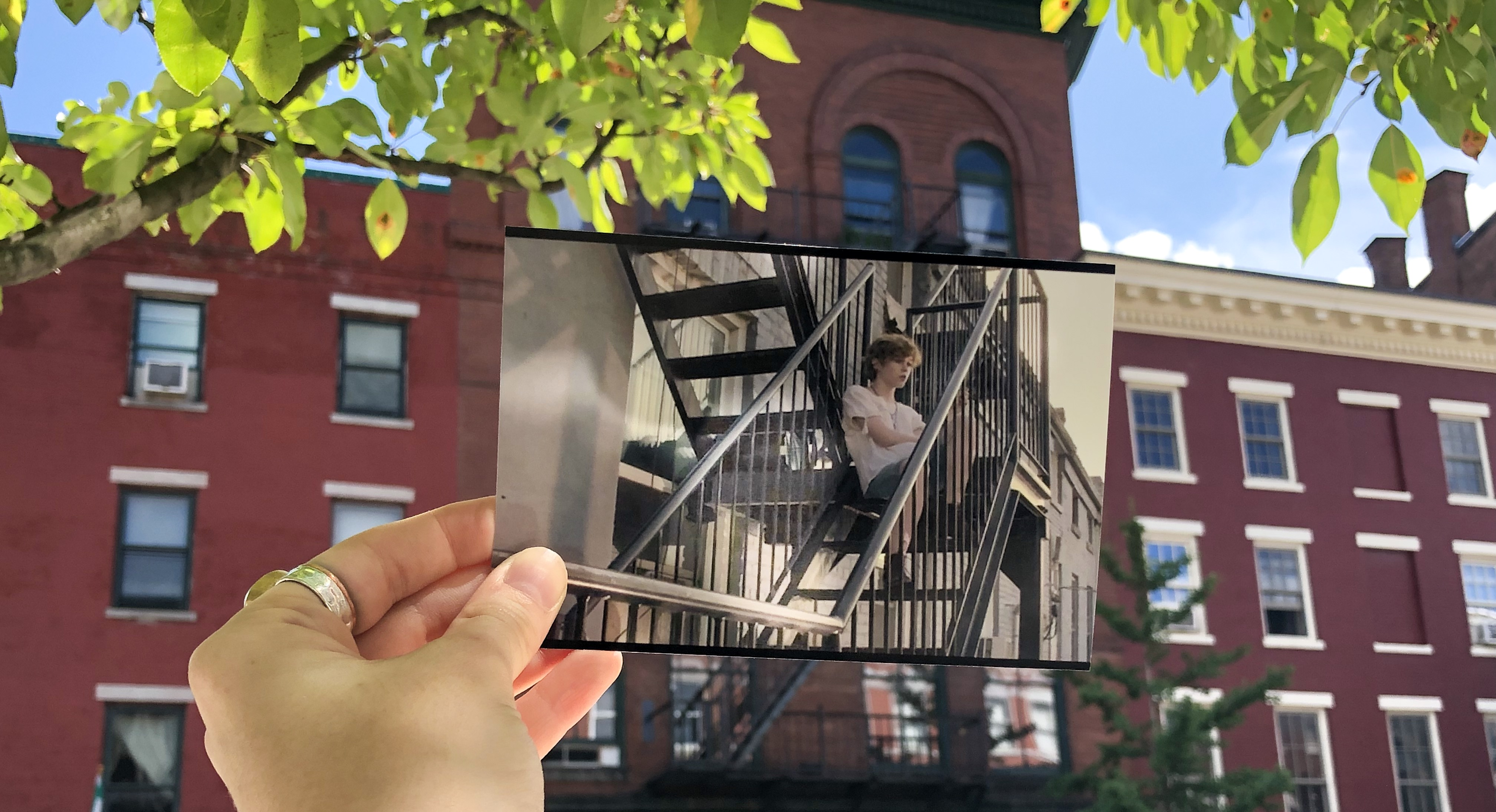 A photo taken from IT 1 of Beverly Marsh sittkng Outside Her Apartment at the actual location that inspired the image.