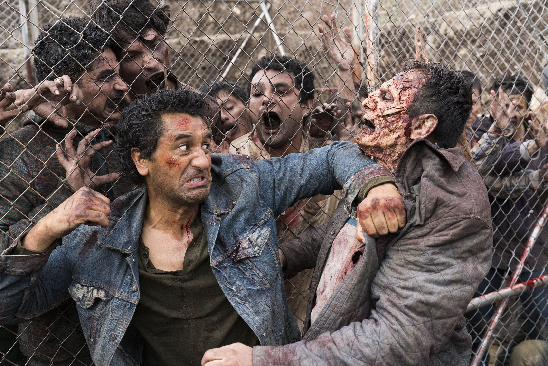 Man fighting off zombie in front a group of fenced zombies - Walking Dead