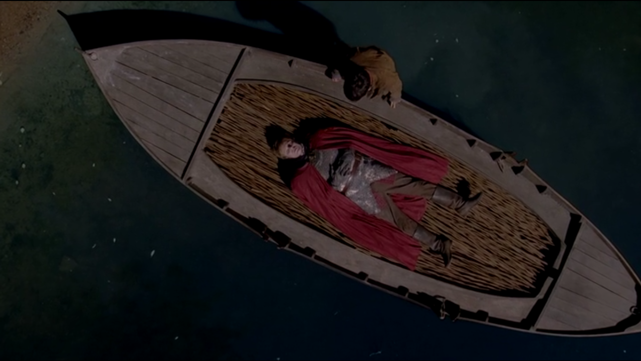 King Arthur's body is placed on a barge to Avalon