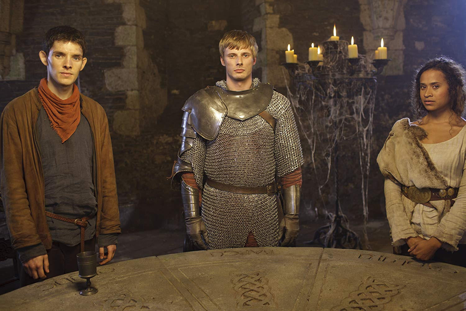 Arthur Pendragon stands at the round table with Merlin and Guinevere