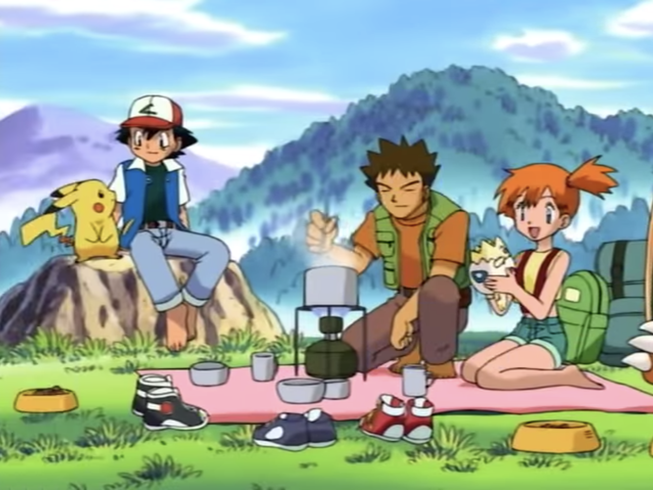 Ash and Pikachu are sitting nearby while Misty is entertains Togepi and Brock cooks a warm meal