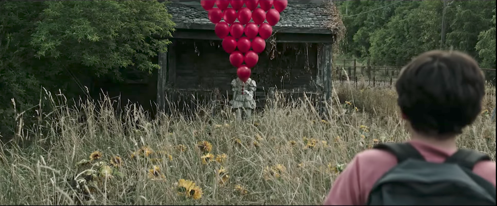 Pennywise holding a large arrangement of red balloons